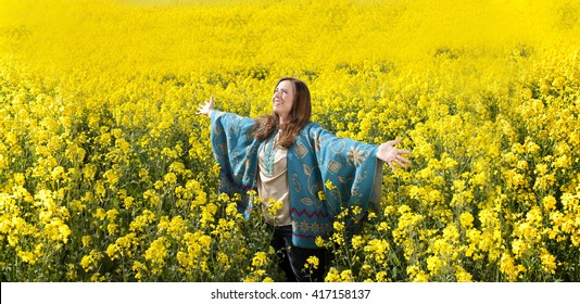 Attractive middle age woman with arms outstretched in flower field