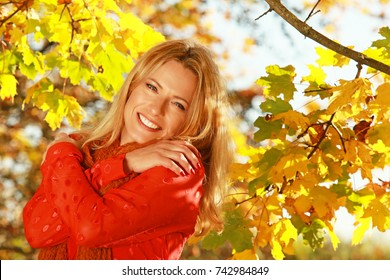 Attractive middle age woman in front of autumn leaves enjoys the last sun beams