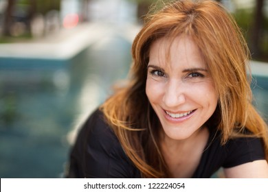 Attractive middle age woman in a outdoor fountain setting.