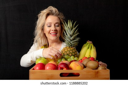 Attractive Middle Aged Blonde Woman With Assorted Fruit Tray