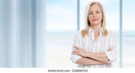 Attractive middle aged business woman in white blouse with folded arms is standing near the window. Summer landscape outside window as background.