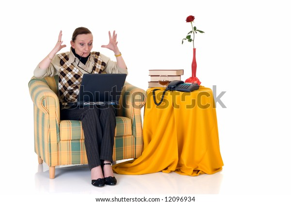 Attractive middle aged businesswoman at home in sofa, working on laptop, white background,  studio shot, reflective surface.