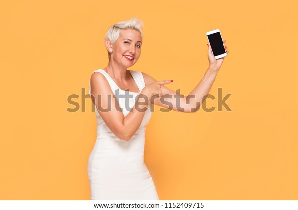 Attractive middle aged businesswoman smiling and showing her mobile phone. Yellow studio background.