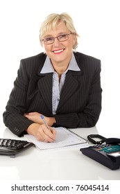 Attractive middle aged caucasian businesswoman in office with telephone and keyboard on her desk, writing on a notebook. Studio shot. White background.