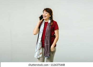 An attractive and middle aged Chinese Asian is talking on her smartphone in a studio. She is smiling as she talks to her friend on her phone and is wearing comfortable but stylish clothes and a scarf.