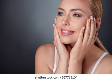 Attractive middle aged lady satisfied with her clean and perfect skin