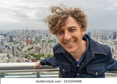 Attractive middle aged man travels in Toyko, Japan and enjoys a beautiful view of the skyline from above.