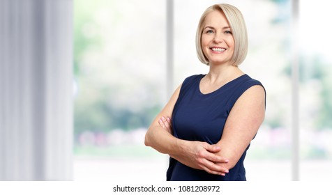 Attractive middle aged woman with beautiful smile near the window.