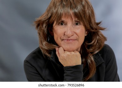 Attractive Middle aged woman with brown layered hair resting her chin on her hand and smiling