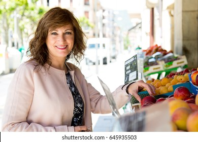 Attractive middle aged woman buying fruit at street market