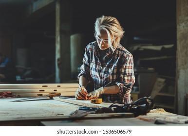 Une femme charpentier d'âge mûr séduisante travaille avec une règle, fait des encoches sur l'arbre en atelier.  Image de féminité moderne. Concept des femmes à motivation professionnelle