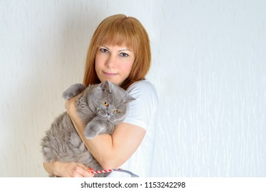 Attractive middle aged woman with cute british shorthair cat resting at home.A woman in the period of menopause. Blond / red hair mature senior female relaxing at home and embracing adorable pet.