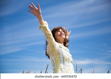 Attractive middle aged woman enjoying nature with arms raised to the blue sky