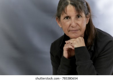 Attractive Middle aged woman with long brown hair resting her chin on her hand and smiling
