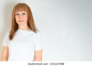 Attractive middle aged woman relaxing at home.A woman in the period of menopause. Blond / red hair mature senior female against the white wall background.