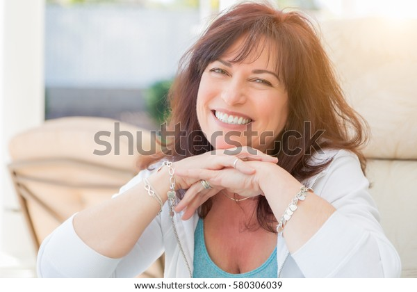 Mulher de meia-idade atraente sorri no pátio.
