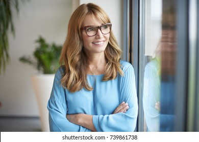 An attractive middle aged woman standing with arms crossed at the window and looking out.
