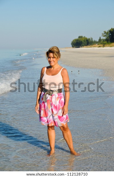 Attractive Middle Aged Woman Walking on the Beach in a Summer Dress