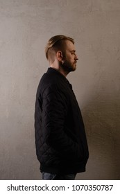 An attractive middle-aged bearded man in a black jacket and jeans stands behind the wall sideways. copy space. deadpan without retouching