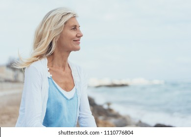 Attractive middle-aged blond woman at the seaside standing smiling as she looks out over the ocean with her hair blowing in the breeze