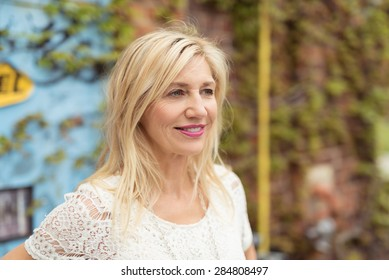 Attractive middle-aged blonde woman with medium-length hair and white laced T-shirt looking away with a serene and jovial facial expression, outdoors, in front of a wall with green climbing plants