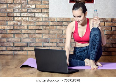 Attractive middle-aged brunette takes a break from exercises while sitting on a gym Mat, drinking water, and overcame instructional videos online