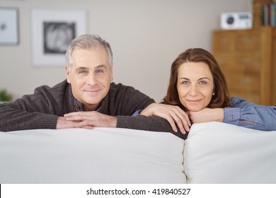 Attractive middle-aged couple with linked arms leaning on the back of a sofa in their living room smiling at the camera