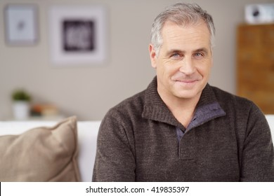 Attractive middle-aged man with a charismatic friendly smile relaxing at home on the sofa, close up head and shoulders