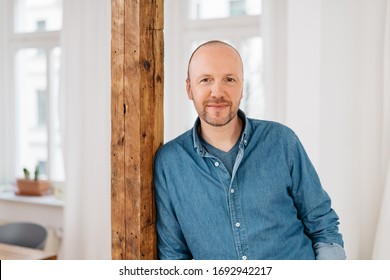 Attractive middle-aged man relaxing at home leaning nonchalantly on a wooden interior post as he smiles quietly at the camera