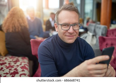 Attractive middle-aged man wearing glasses sitting in a restaurant holding his mobile phone as he smiles at the camera