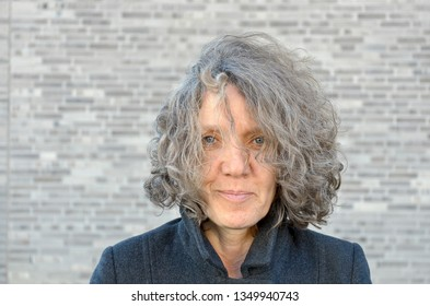 Attractive middle-aged woman with curly hair and a quiet smile standing in front of a grey brick wall outdoors in a head and shoulders portrait