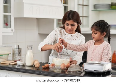Attractive middle-aged woman and her cute little daughter beating eggs and flour with whisk while making delicious pie at home, interior of small kitchen on background