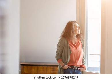 Attractive middle-aged woman standing with her hands in her pockets of her jeans staring out of a window with a thoughtful expression and copy space