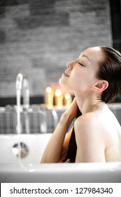 Attractive Mixed Asian Female enjoying bath with eyes closed