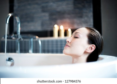 Attractive Mixed Asian Female enjoying the bath with candles
