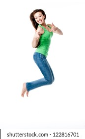 Attractive Mixed Asian female in green top jumping with thumbs up