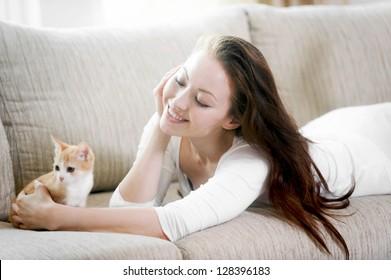 Attractive mixed asian woman admiring her kitten