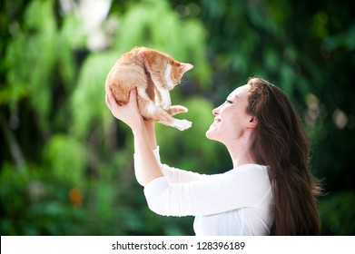 Attractive mixed asian woman holding kitten close to face