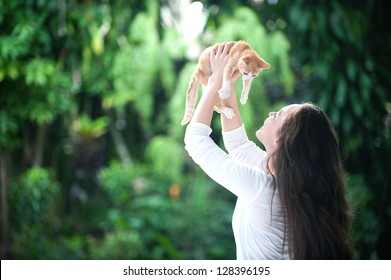 Attractive mixed asian woman holding kitten high with both hands