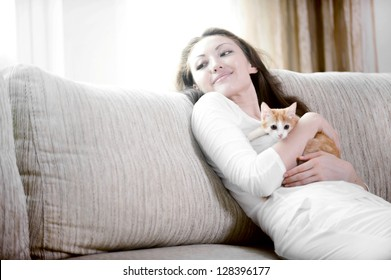 Attractive mixed asian woman hugging kitten on sofa