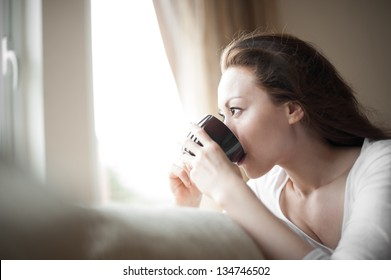 Attractive mixed female lifestyle drinking a cup of coffee looking out