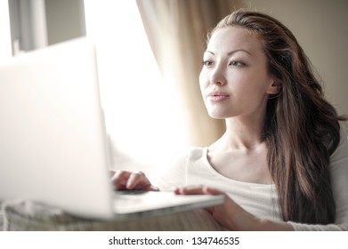 Attractive mixed female lifestyle paying attention while typing
