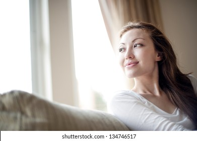 Attractive mixed female lifestyle relax on the sofa looking out the window