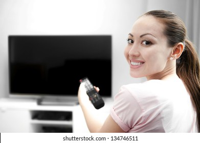 Attractive mixed female lifestyle smiling holding the control