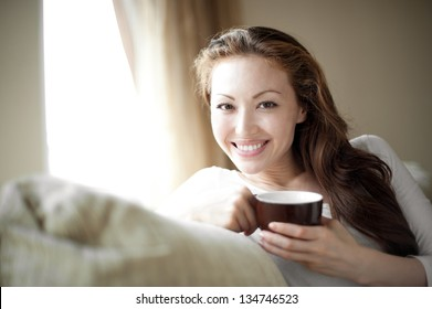 Attractive mixed female lifestyle smiling with a cup in hand
