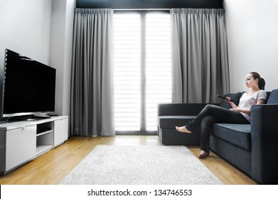 Attractive mixed female lifestyle watching tv at home