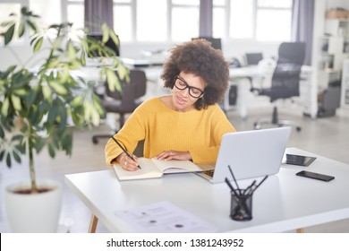 Attractive mixed race businesswoman dressed casual taking notes in notebook while sitting in modern office. On desk laptop, tablet and smart phone.
