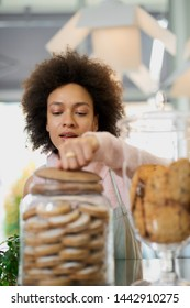 Attractive mixed race employee in pink turtleneck sweater and with apron opening jar with cookies. Pastry shop interior.