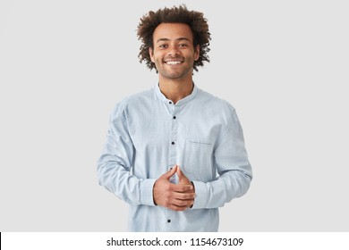 Attractive mixed race male with positive smile, shows white teeth, keeps hands on stomach, being in high spirit, wears white shirt, rejoices positive moments in life. People and emotions concept