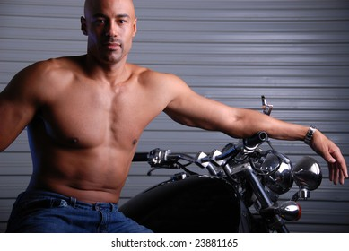 Attractive mixed race man wearing jeans and no shirt sitting on a motor bike.